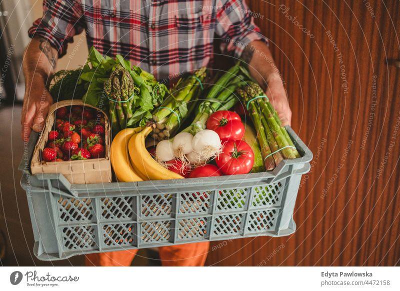 Mann, der eine Obst- und Gemüsekiste ausliefert Erwachsener Kasten kaufen Essen zubereiten Coronavirus Kurier Versand Lieferbox Auslieferer Diät Tür