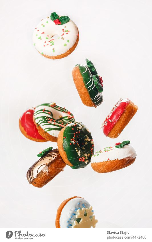 Fliegende Weihnachtskrapfen. Bunte Krapfen mit Streuseln fallen oder fliegen in Bewegung gegen weißen Hintergrund 3d Amerikaner Bäckerei Brot Frühstück Kuchen