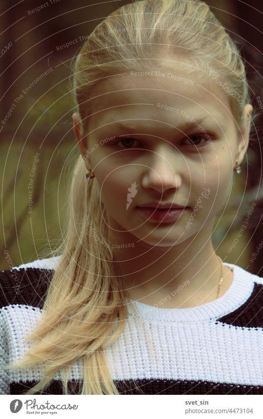 Porträt eines blonden Mädchens mit vollem Gesicht vor dem Hintergrund des Herbstwaldes. jung im Freien Blick Teenager Schönheit natürlich Behaarung Dame Model