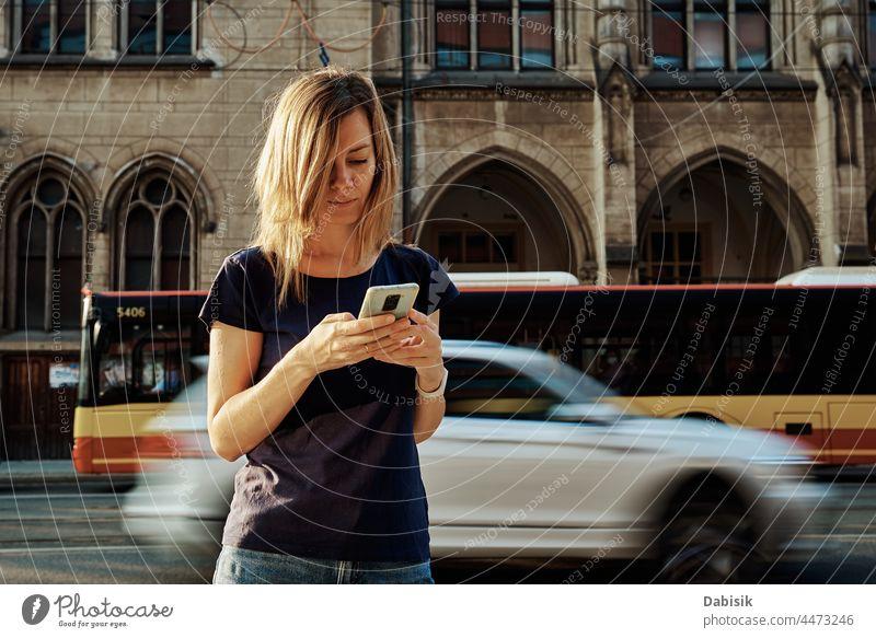 Frau benutzt Smartphone auf einer Straße in der Stadt Mobile laufen Lifestyle Kommunizieren online Porträt Telefon benutzend Fröhlichkeit tragbar Information