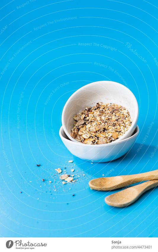 Frühstücksflocken in zwei Schüsseln auf einem blauen Hintergrund. Müsli Hintergrund neutral Löffel Lebensmittel Haferflocken getrocknet Diät Ernährung