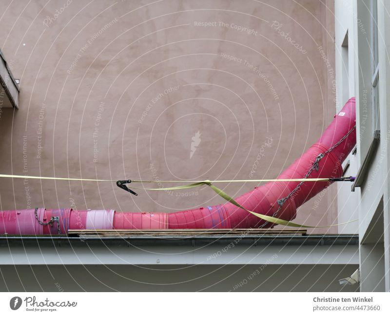 konstruktiv   Renovierung einer Wohnung. Aus einem Fenster hängt eine rosafarbene Schuttrutsche und liegt auf dem angrenzenden Flachdach Bauschuttrutsche