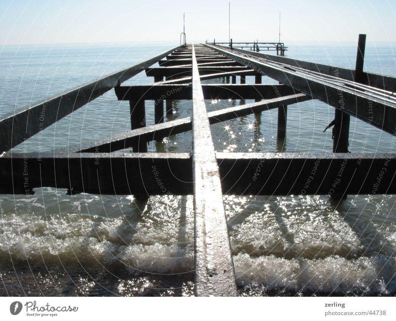 Bootssteg Wasser Sonne Meer glänzend Gleise Anlegestelle