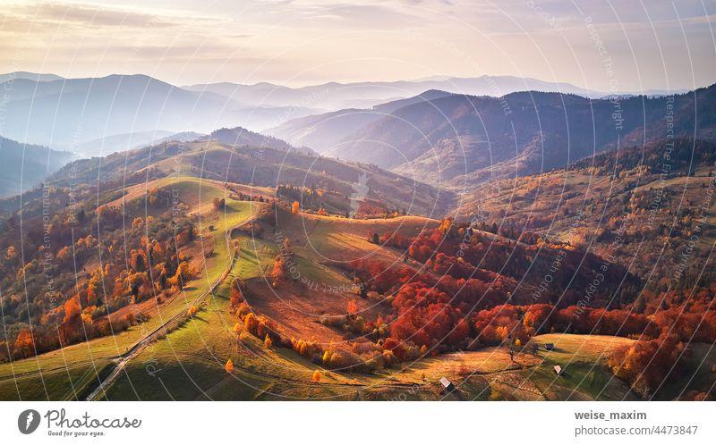 Schöne Berg-Herbstlandschaft mit Wiese und buntem Wald. Rote, gelbe und orangefarbene Bäume an den Hängen. Landschaft Berge fallen farbenfroh Natur Hintergrund