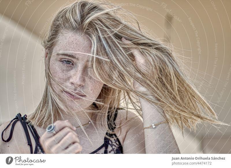 Junge blonde Frau mit sommersprossigem Gesicht und im Wind wehendem Haar freck sommersprossiges Gesicht Haare blasen Haare wehen im Wind hübsch grüne Augen