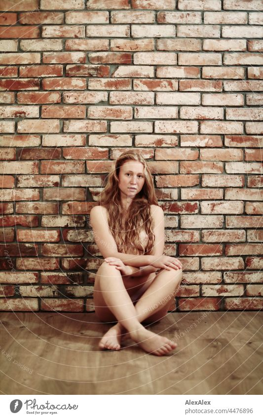 Ganzkörperbild einer nackten, jungen Frau mit Sommersprossen und roten Haaren, die vor einer Backsteinwand auf dem Boden sitzt Porträt nah Nähe Ausstrahlung