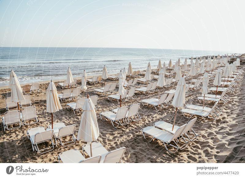 leerer Strand mit zugeklappten Sonnenschirmen und leeren Sonnenliegen Sonnenschein Liege Liegestuhl Ferien & Urlaub & Reisen Meer Sommer Erholung Sommerurlaub