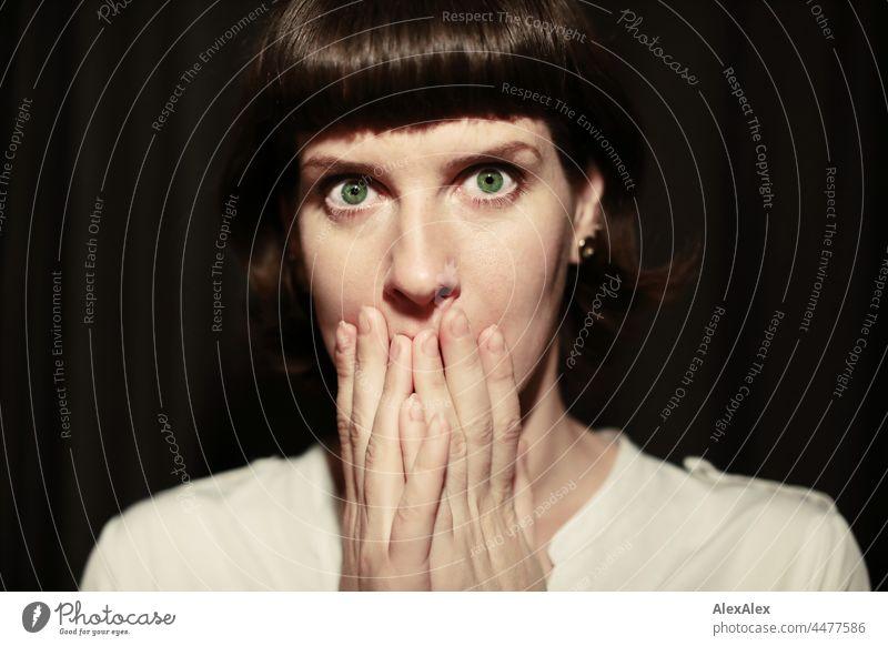 Junge Frau mit intensiven grünen Augen schaut erschrocken in die Kamera und hält sich die Hände über den Mund junge Frau erstaunt schön schlank grünäugig