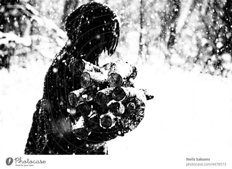 menschliche Silhouette, Schneesturm, Feuerholz tragen, arbeiten und hoffen, dass es warm wird. Nicht für Weihnachtskarten. Brennholz schwarz auf weiß