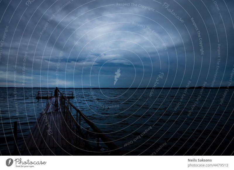 Holzsteg auf dem See in der blauen Stunde des Sonnenuntergangs, menschliche Silhouette. Trail ist aus Holzplatten, Sicherheitsgeländer auf der rechten Seite gemacht. Schöne bewölkten Himmel in weichem Licht
