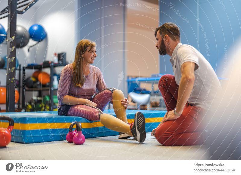 Frau mit Beinprothese im Gespräch mit einem Physiotherapeuten Physiotherapie Tatkraft Wiederherstellung Rehabilitation Stärke Training Beine Übung Fitness Sport