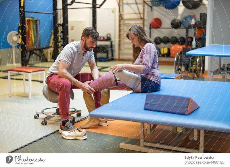 Physiotherapeutin hilft junger Frau mit Beinprothese Physiotherapie Tatkraft Wiederherstellung Rehabilitation Stärke Training Beine Übung Fitness Sport