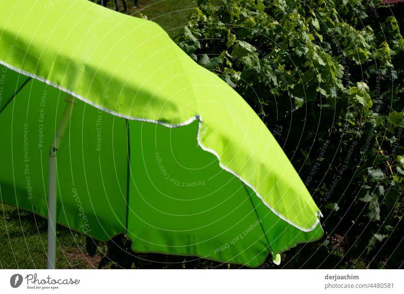 Die Sonne scheint. Da wird doch gleich der Sonnenschirm heraus geholt und auf gespannt.Im Hintergrund grüne Blätter. Schirm Außenaufnahme Menschenleer
