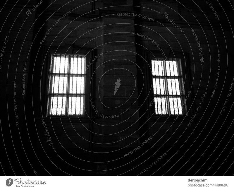 Zwei vergitterte hell erleuchtete Fenster in dunkler Nacht. fenster Fassade architektur Haus Gebäude alt historisch bauwerk brauchtum backstein bauwesen nacht