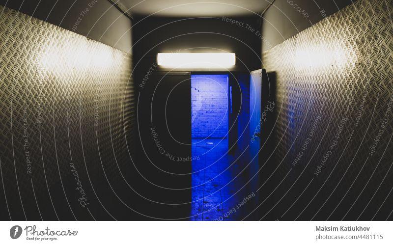 Blaues Licht hinter einer offenen Tür in einem geheimnisvollen Korridor. Geheimzugang blau Eingabe Gang Ausfahrt industriell Flucht Stahl Industrie Wand Metall