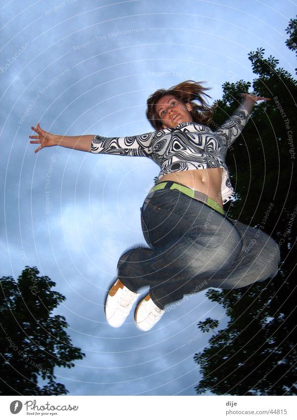 Freudensprung Frau Himmel Baum blau Wolken springen Bewegung Jeanshose üben