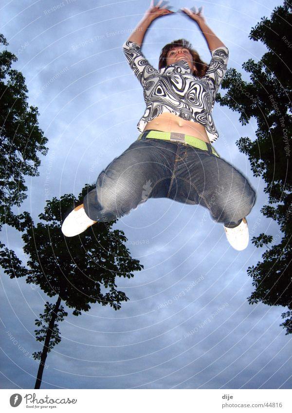 Froschsprung Frau Himmel Baum blau Wolken springen Bewegung Jeanshose üben