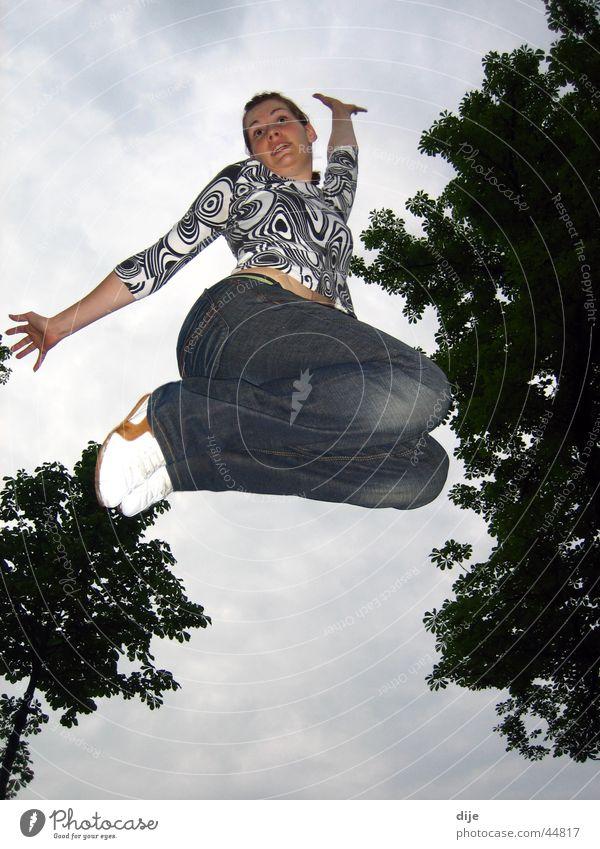 Der eleganter Sprung Frau Himmel Baum blau Wolken springen Bewegung Jeanshose üben