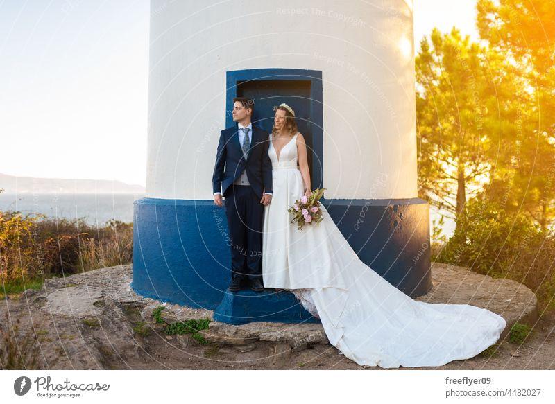 Ein Ehepaar an der Tür eines Leuchtturms Hochzeit Ehemann Ehefrau Bekleidung Liebe Feier Textfreiraum Paar heterosexuell Braut striegeln Wald Baum