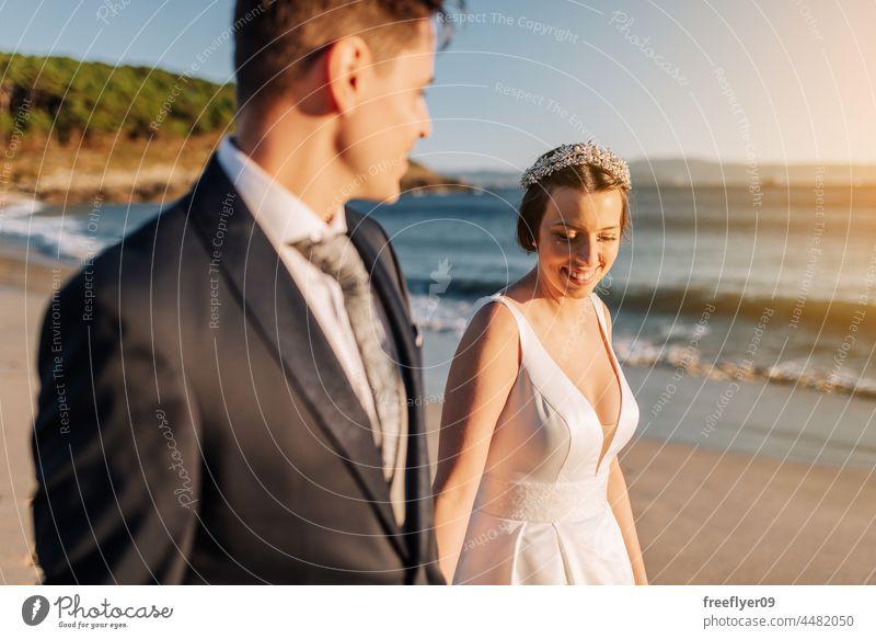 Ein Ehepaar geht am Strand spazieren Hochzeit Ehemann Ehefrau Bekleidung Liebe Textfreiraum Meer Sonnenuntergang Paar heterosexuell Braut striegeln Wald Baum