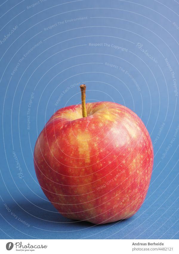 Ein frischer roter Bio-Apfel auf einem blauen Studiohintergrund Äpfel organisch Haufen Ackerbau appetitlich Produkt Ernährung geschmackvoll Erfrischung