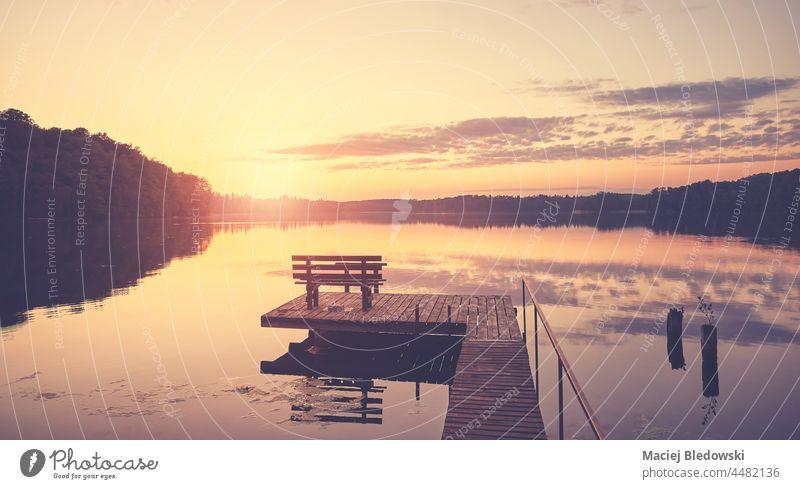 Malerischer Sonnenuntergang über dem See mit Holzbank auf dem Steg. Himmel Wasser Landschaft Bank Sommer hölzern im Freien niemand Pier reisen
