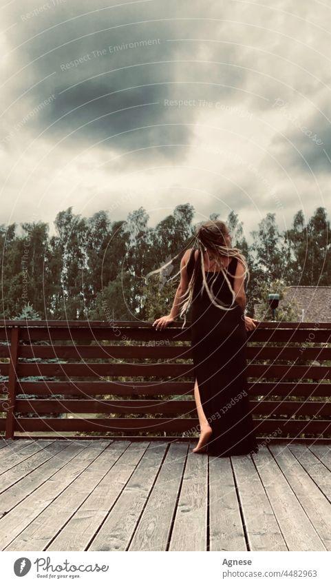 Mädchen mit Dreadlocks vor dem Sturm Frau Rastalocken Wein Weinglas schwarzer Himmel Unwetter Gewitterwolken stürmisch Gewitterhimmel stürmische Atmosphäre Wind