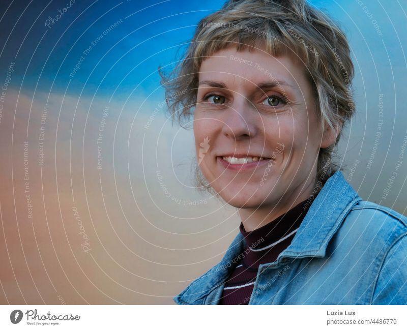 Blaue Stunde, fröhliches Lachen: Frau mit kurzen Haaren blickt vergnügt in die Kamera lächeln lächelnd kurzhaarig hübsch charmant Lächeln Glück Porträt schön