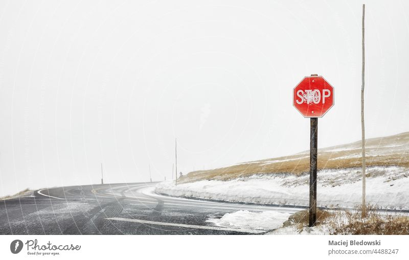 Stoppschild an einer Bergstraßenkreuzung während eines Schneesturms, selektiver Fokus, Colorado, USA. Straße stoppen Zeichen Verkehr Berge Laufwerk Gefahr