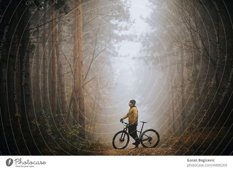 Junger Mann macht eine Pause beim Radfahren durch den Herbstwald Aktion aktiv Aktivität Abenteuer Athlet Fahrrad Radfahrer Biker Zyklus Übung extrem schnell