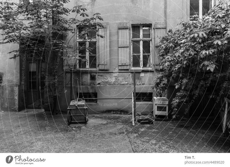 ein alter Hinterhof mit Teppich Klopfstange und Fahrradanhänger Prenzlauer Berg Berlin Altbau bnw Hof Innenhof Menschenleer Stadt Tag Stadtzentrum Haus Altstadt