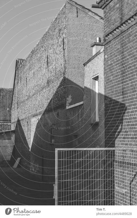 Ein Dorfhof mit Schatten in Brandenburg Spreewald bnw Hof Außenaufnahme Tag Menschenleer Haus Gebäude alt historisch Fenster Altbau Altstadt Architektur Bauwerk