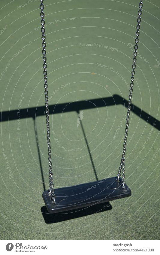 Leere Schaukel auf Kinderspielplatz grün schwarz Spielplatz menschenleer verlassen spielen Außenaufnahme Kindheit Lockdown schaukeln trist Lebensfreude