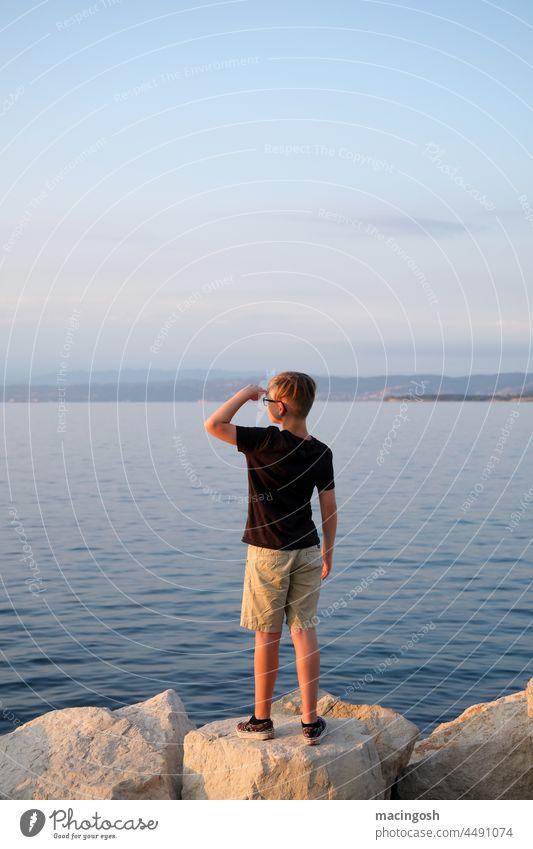 Junge beobachtet den Sonnenuntergang am Meer Jugendlicher beobachten Idylle romantisch Romantik Abend Abendstimmung Sonnenlicht Abenddämmerung Dämmerung Himmel