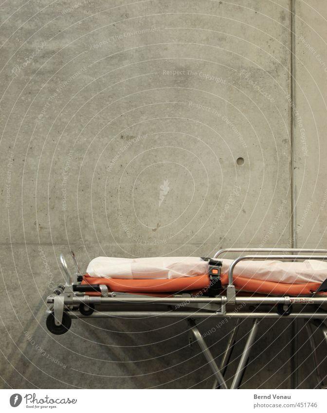 Krankenwagen weiß rot schwarz Wand Mauer grau liegen Beton Liege Bett Rad Röhren silber Decke tragen parken