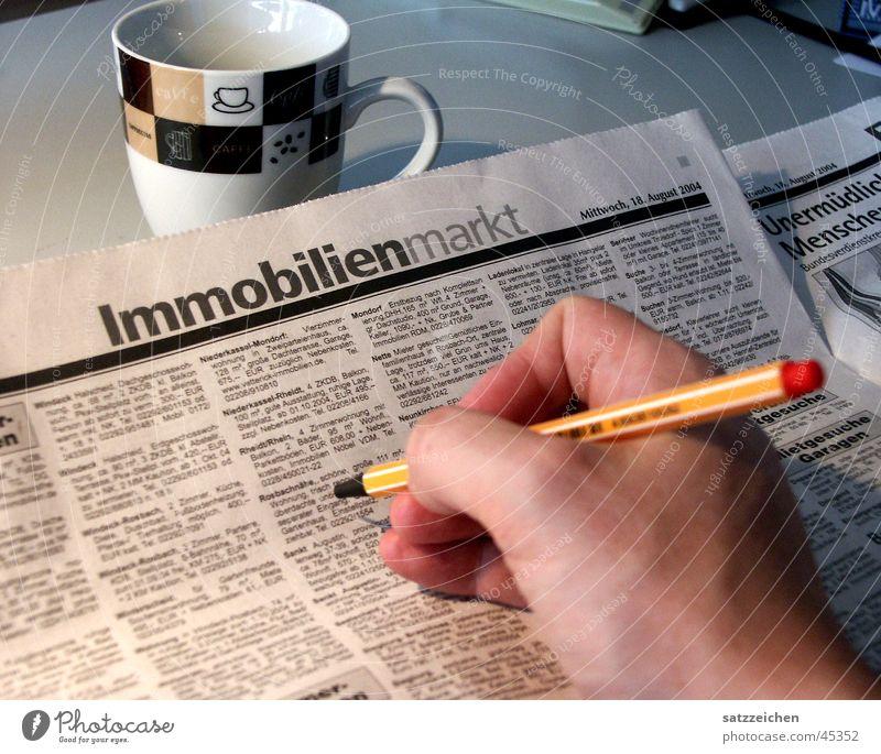 Traumhaus gesucht Hand Gebäude Haus Zeitung Schreibtisch Schreibstift Zeitschrift Inserat Kaffeetasse Traumhaus Immobilienmarkt