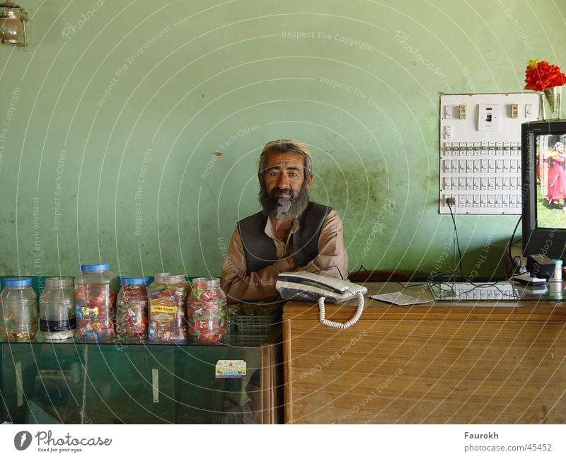 Verkäufer in Nepal Mann alt Ladengeschäft Süßwaren Indien Theke Nepal