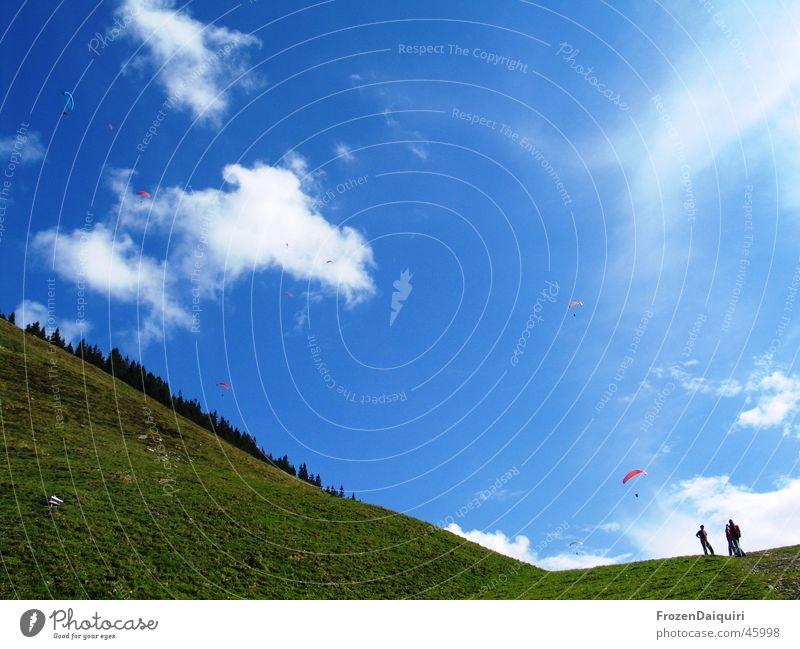 Ganz leiser Flugverkehr Wolken mehrfarbig Gleitschirm Luft weiß Berghang Schweben wandern Westendorf Bundesland Tirol Himmel paragleiter blau Erde