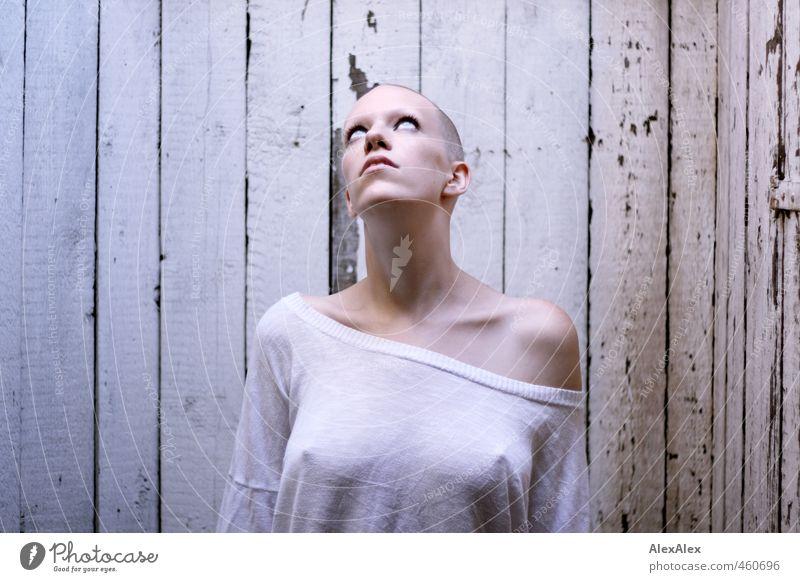 Junge Frau mit dünnem T-Shirt vor Bretterwand schaut nach oben ins Licht vom Dach Jugendliche Kopf Brustwarze Schulter Sommersprossen 18-30 Jahre Erwachsene Top