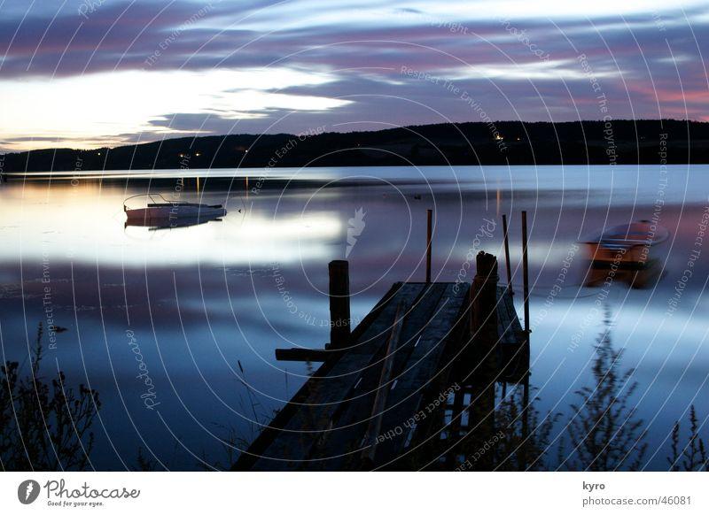 märchensee See ruhig Langzeitbelichtung Blende kalt Wasserfahrzeug Steg Holz Strand Reflexion & Spiegelung Wolken schlechtes Wetter nass dunkel Nacht Glätte