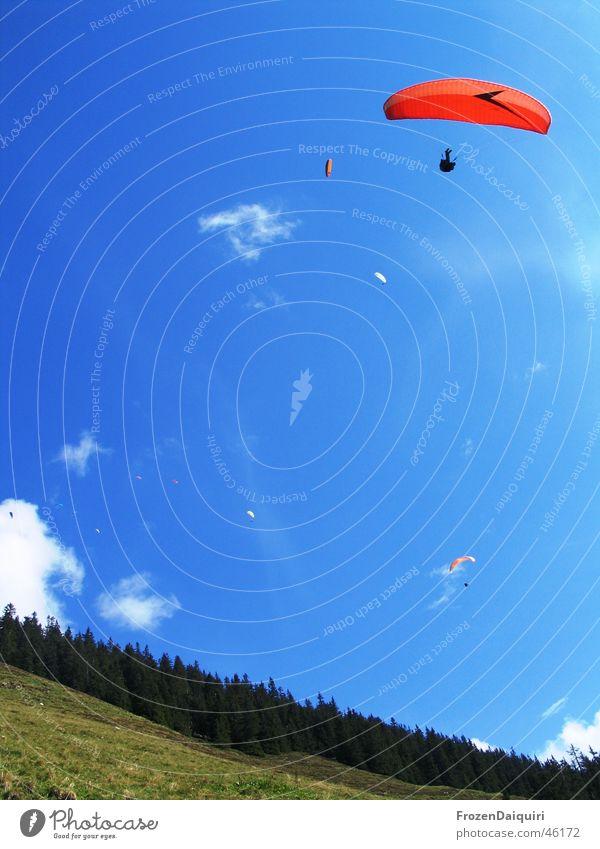 Ganz leiser Flugverkehr #2 Wolken mehrfarbig Gleitschirm Luft weiß Berghang Nadelwald Baum Gras Wiese Schweben wandern Westendorf Bundesland Tirol Himmel
