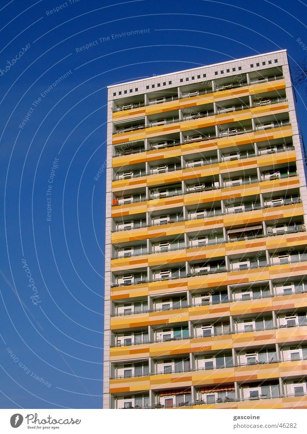 Plattenbau Haus gelb Hochbau blau Balkon mehrfarbig mehrere Gebäude Schnellbau trist Außenaufnahme hoch Blauer Himmel Kontrast Farbe viele Ordnung Architektur