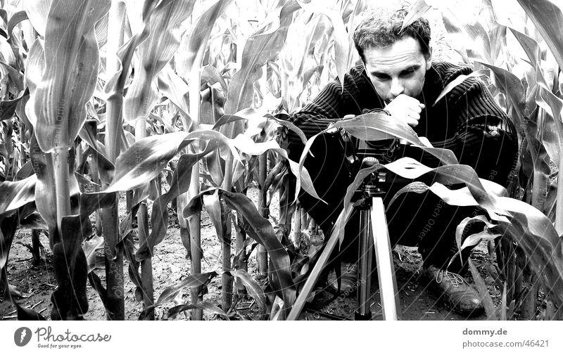 der Fotograf Mann hocken Feld schwarz weiß Stativ Hand Hose Jacke Trauer Denken zdenek sitzen Schwarzweißfoto Mais Fotokamera milolta konica Haare & Frisuren
