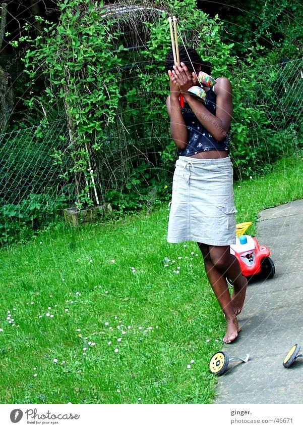 Versteckspiel - Peekaboo Mensch grün Mädchen Wiese Garten stehen Spielzeug Rock verstecken Schüchternheit verdeckt Afrikaner Hautfarbe zurückhalten Kind Steinplatten