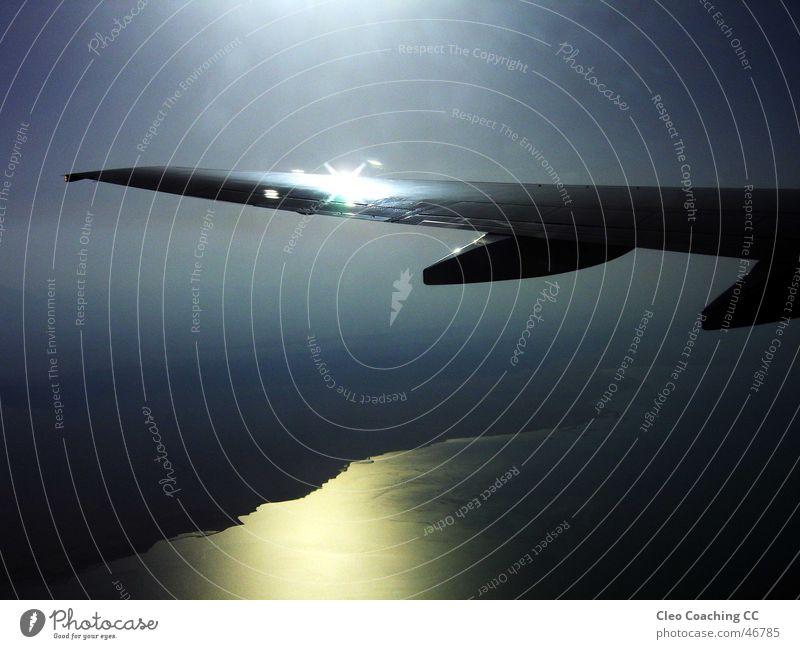 Durch das Flugzeugfenster Wasser Himmel Sonne Freude Ferien & Urlaub & Reisen Wolken dunkel grau Traurigkeit Stimmung glänzend Flugzeug Nebel Geschwindigkeit Trauer Elektrizität