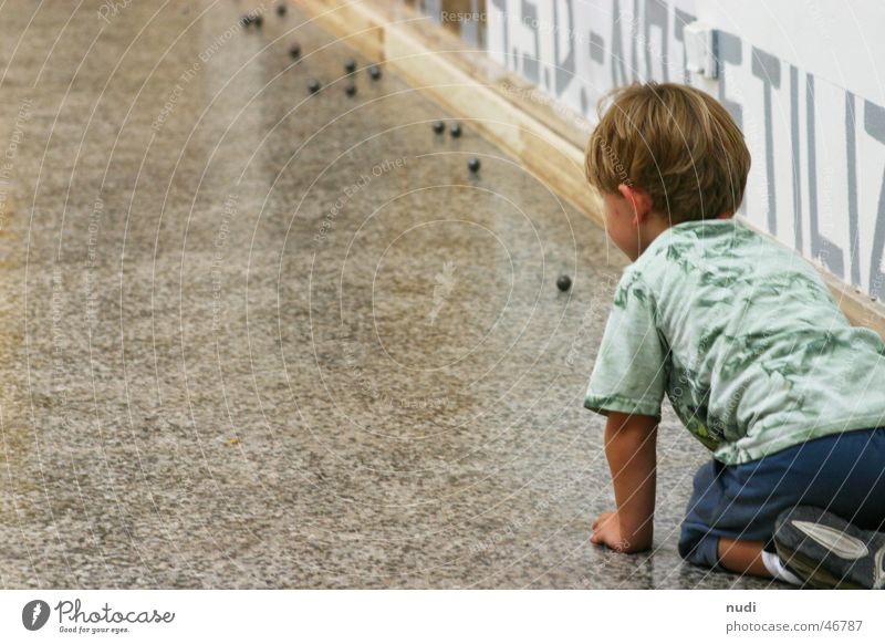 Faszination Kugel Kind Junge Spielen T-Shirt blond Wand Venedig Freude Bodenbelag auf den knien kunst bienale boy play fun Rückansicht