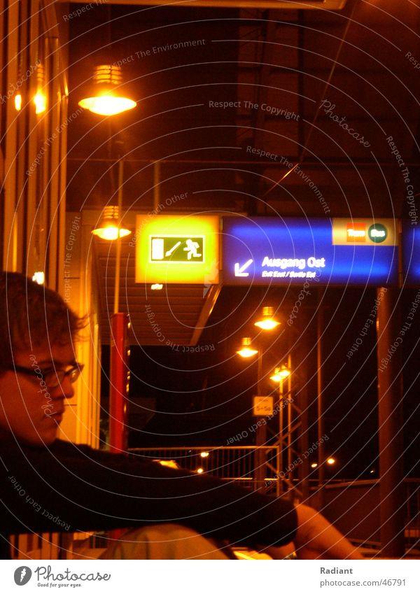 please wait Haltestelle Verspätung Jugendliche Mann Brille Gleise Nacht dunkel Licht Lampe Notausgang gehen grün Ausgang Dresden wegfahren Außenaufnahme