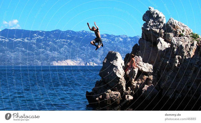 der Sprung Mann Hand Sonne Meer blau Wolken springen Stein Beine fliegen Felsen gefährlich bedrohlich Kroatien Adria