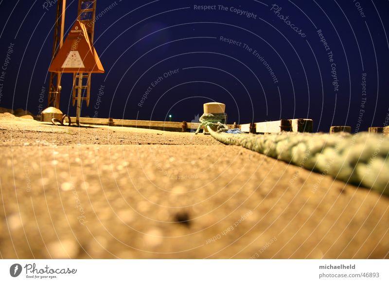 Das zieht sich lange hin Mole Anlegestelle dunkel Nacht Seil Rettungsring Stab Poller Asphalt Beton Froschperspektive Licht Hafen Abend Leiter Strommast
