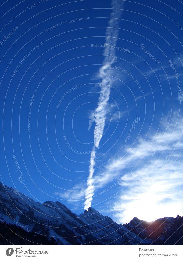 Vorabendstimmung in den Schweizer Alpen Himmel Sonne blau Wolken Schnee Berge u. Gebirge Kondensstreifen